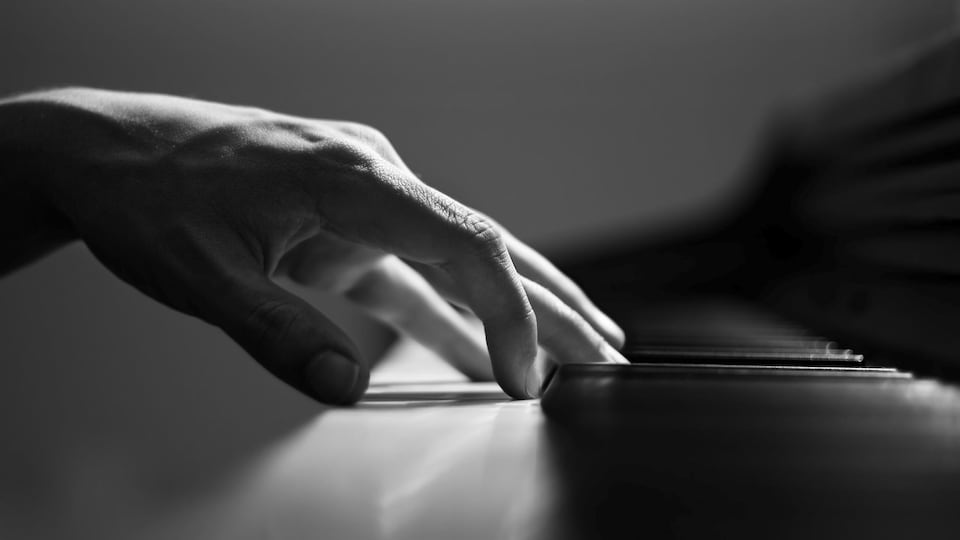 Des mains jouent sur un piano.