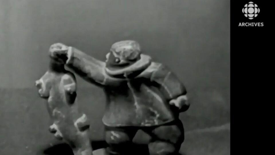 Sculpture inuit montrant un chasseur tenant un phoque par la tête.