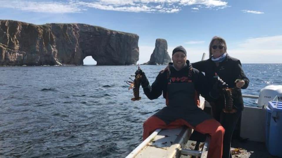 Jimmy Lepage assis sur navire de pêche devant le rocher Percé tient un homard dans chaque main en compagnie d'une femme.