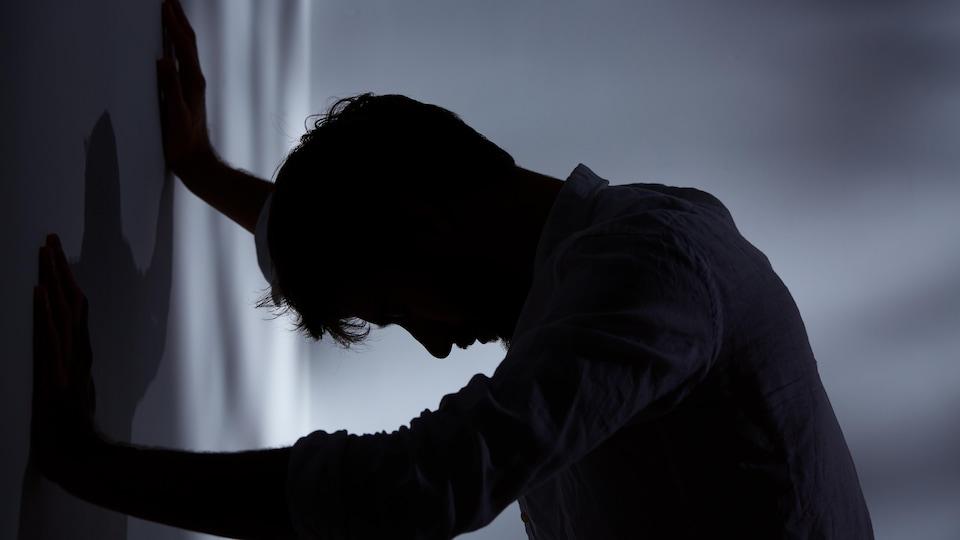 Un homme appuyé sur un mur dans une pièce sombre.