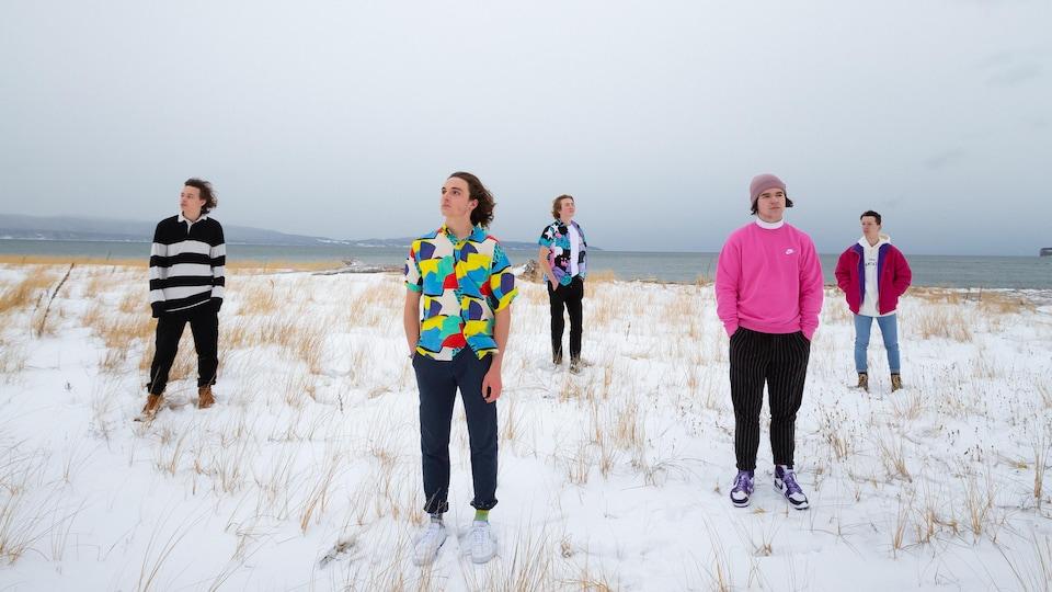 Cinq adolescents sur la plage enneigée d'Haldimand, en Gaspésie.