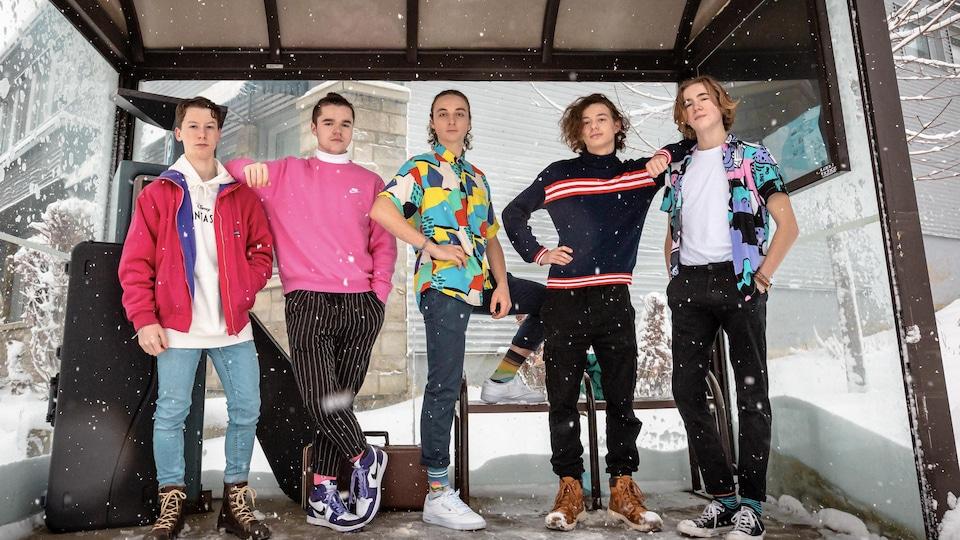 Une groupe de cinq jeunes dans un abribus à Gaspé.