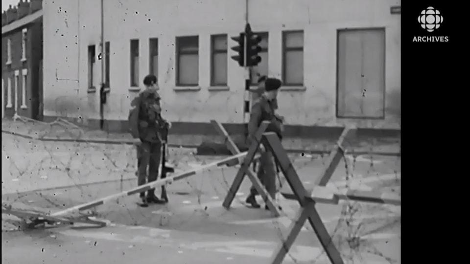 Trois soldats britanniques installent un barrage de barbelés dans une rue de Derry, en Irlande du Nord.