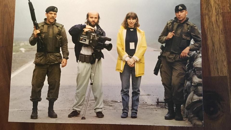 La journaliste est entourée de son caméraman et de deux soldats.
