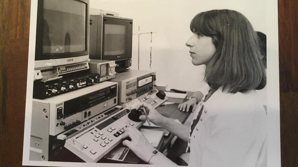 La journaliste est assise devant des ordinateurs.