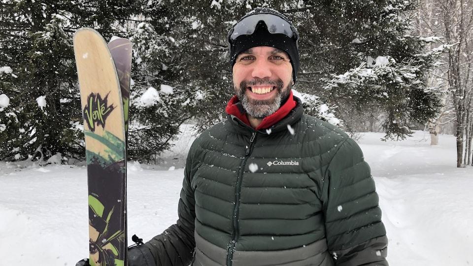 Jacob Racine pose avec ses skis, devant un paysage enneigé.