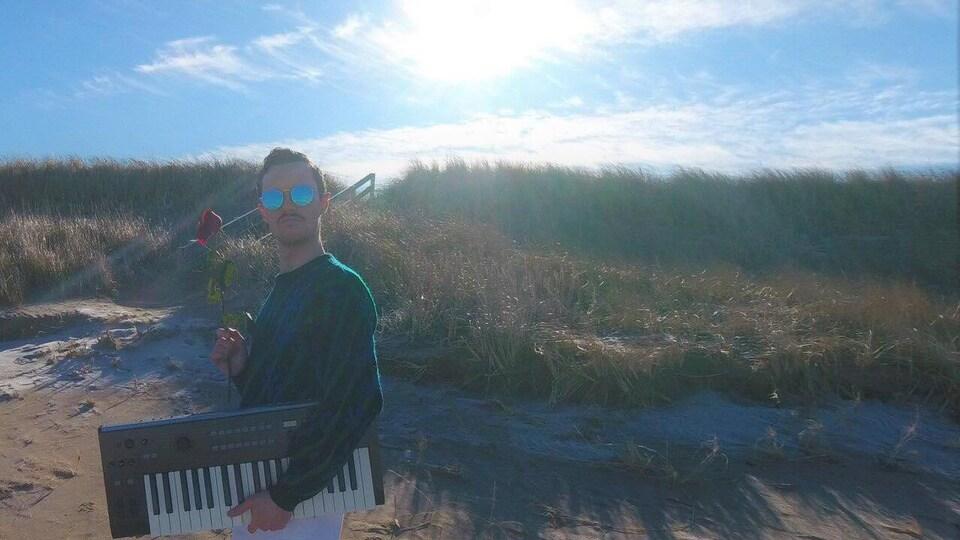Jalapeño Papa qui porte des lunettes fumées sur une plage avec en main une rose et tenant un clavier sous son bras.