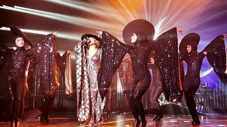 La star américaine Jennifer Lopez entourée de ses danseurs tous vêtus de costumes étincelants brodés de diamants Swarovski de type haute couture, dans un numéro de groupe sur la scène du casino Planet Hollywood de Las Vegas en juin 2016.