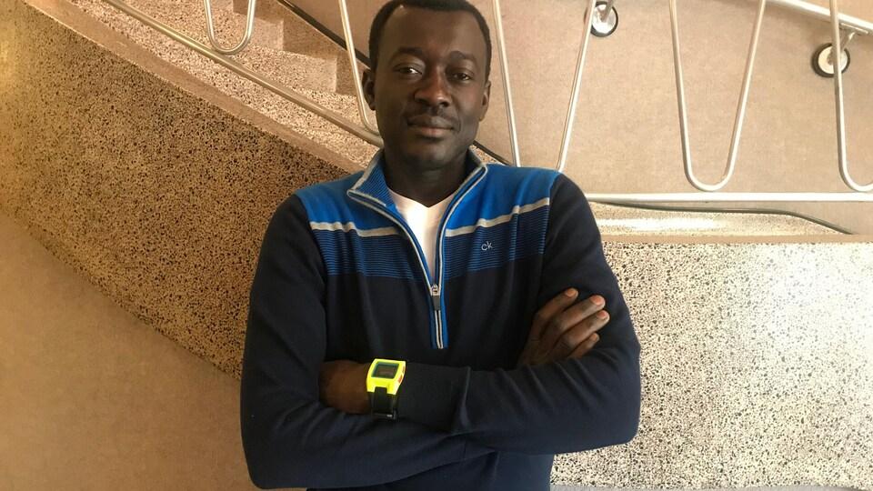 Un jeune homme africain, debout les bras croisés devant un escalier.