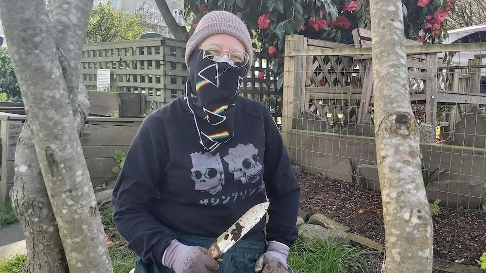 Madeleine Walton en train de jardiner. Elle porte un bonnet sur sa tête, mais aussi un masque de protection au niveau du visage.