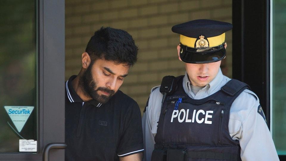 Jaskirat Singh Sidhu est escorté par un policier.