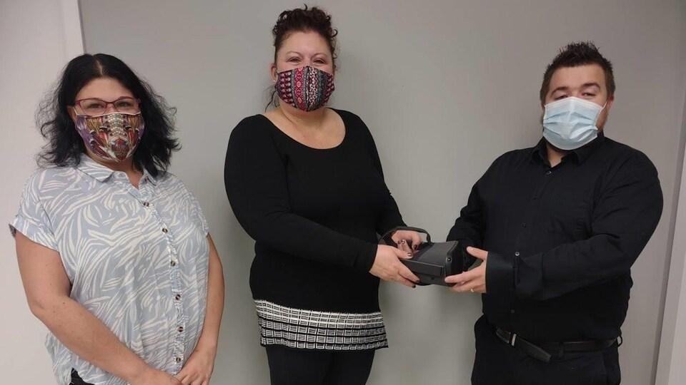 Jason Michaud tend un masque de réalité virtuelle à l'une des employées du Centre de formation de Cochrane-Iroquois Falls.