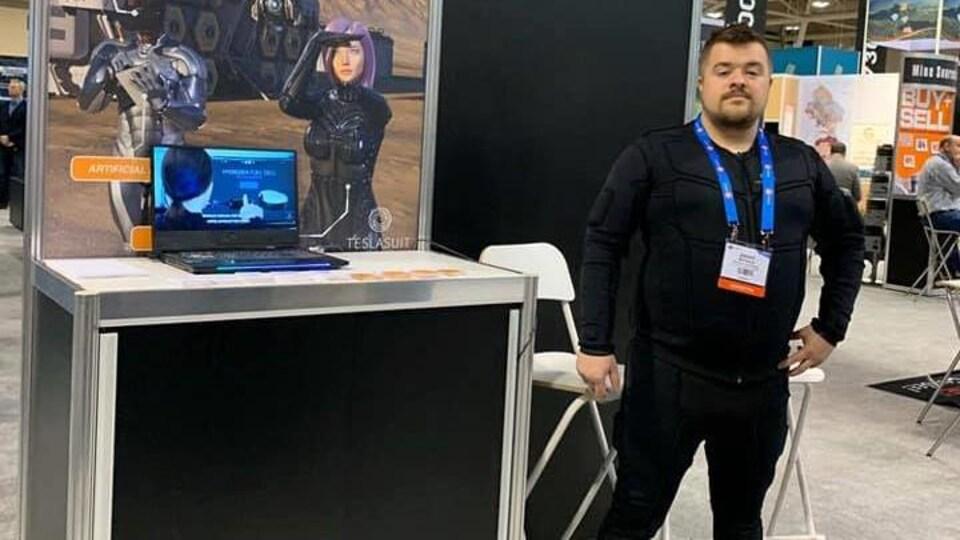 Jason Michaud debout devant un kiosque de Stardust Technologies, vêtu du Tesla Suit.