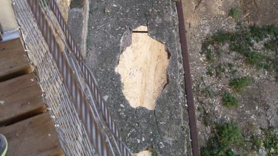 Une vieille passerelle de béton parsemée de gros trous.