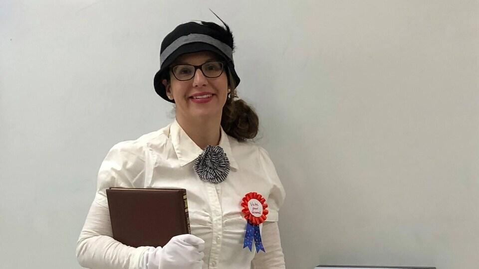 Christine Pagé vêtue de son costume de suffragette avec l'affiche «les années folles».