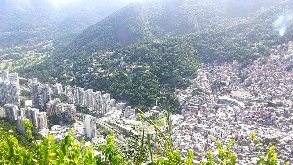 Vue de haut, on voit la ville à la gauche et la favela à la droite.
