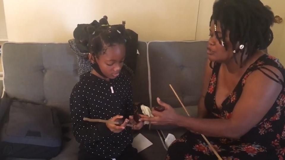 Elle pointe l'instrument de l'élève. Toutes les deux sont assises sur un divan.