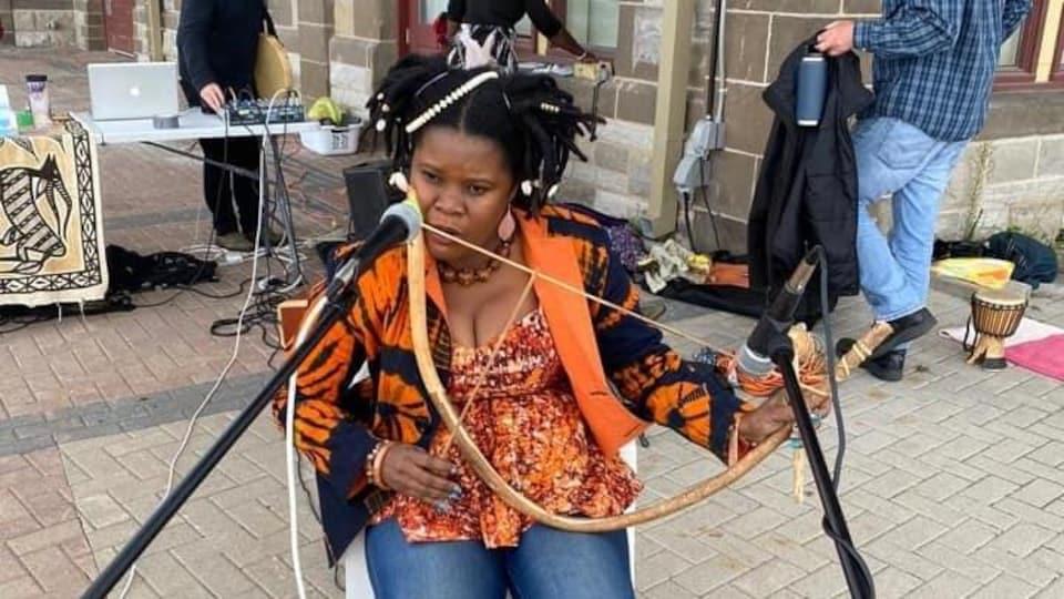 Assise sur une chaise à l'extérieur, Gisèle Gbobouo joue l'instrument.