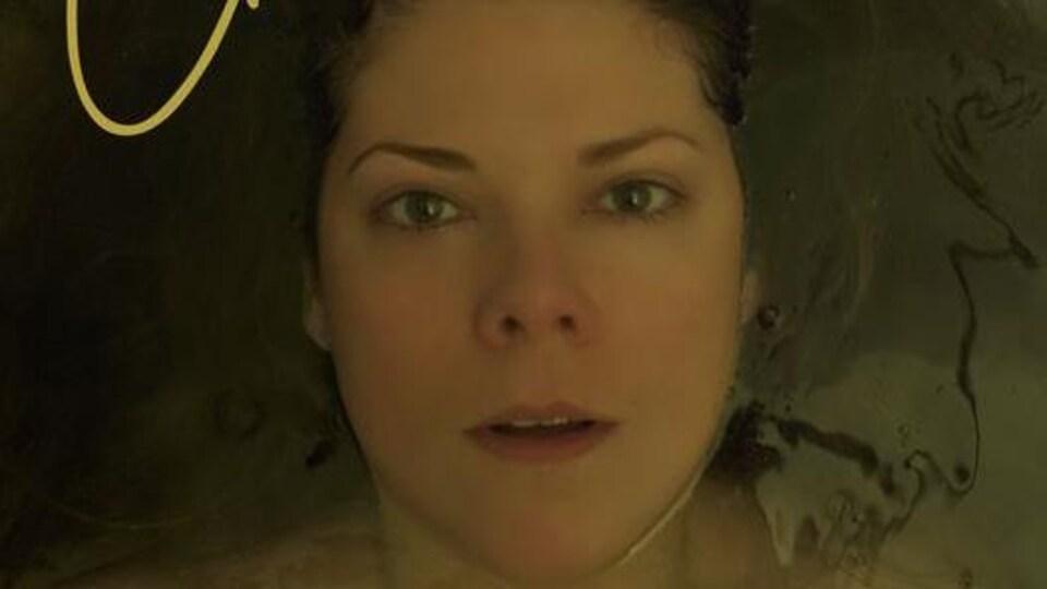 Photo portrait de son visage alors qu'elle baigne dans un bain.
