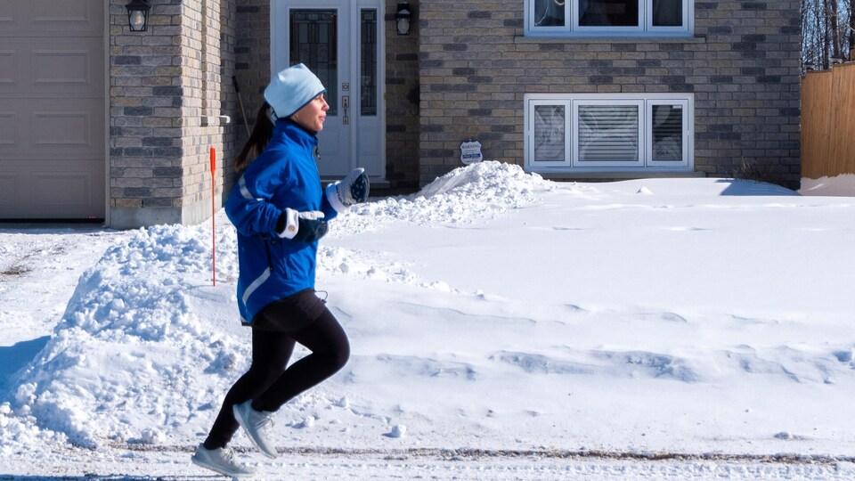 La femme court dans des rues enneigées.