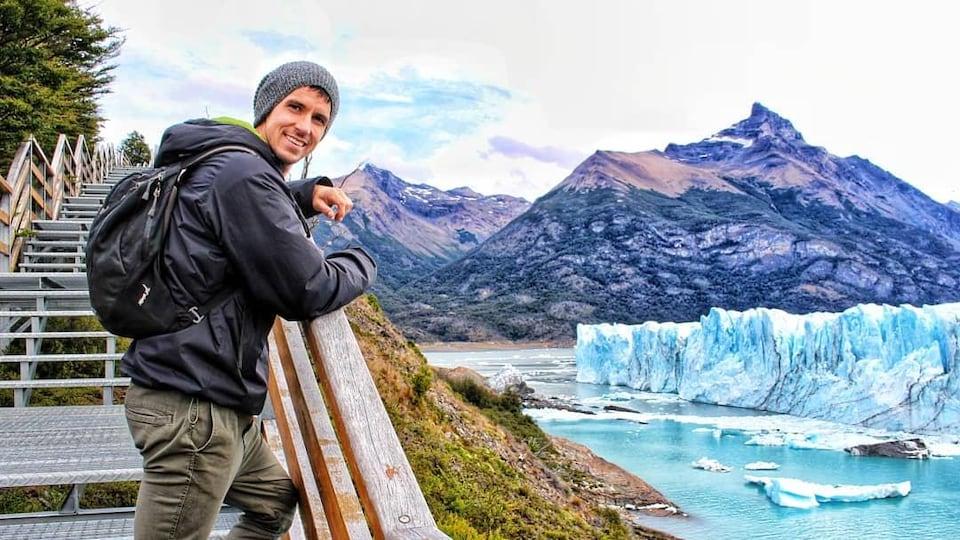Un homme debout sur la passerelle devant le glacier.