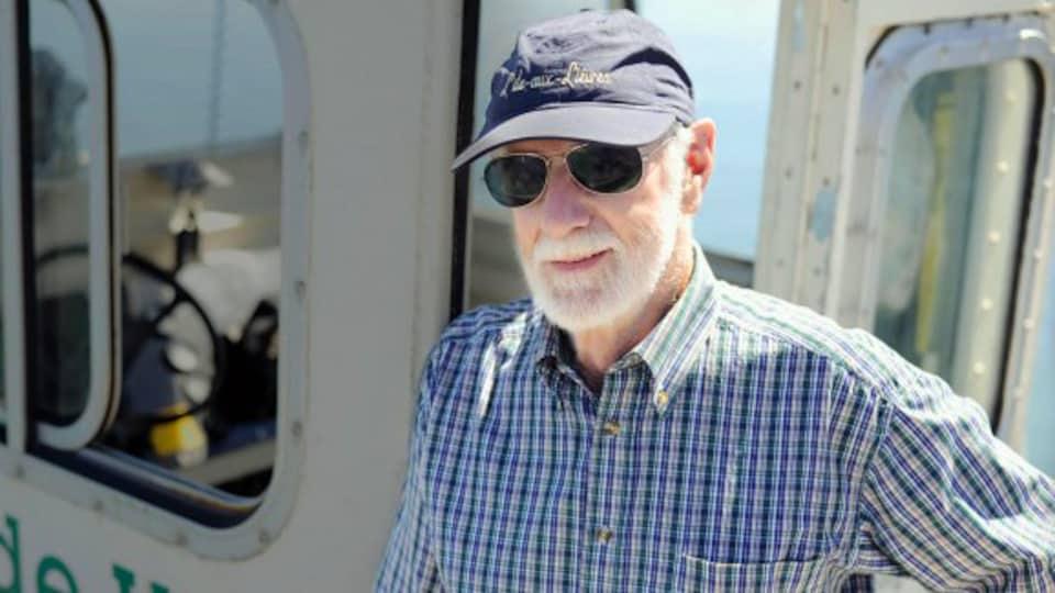 Un homme avec une casquette bleue et des lunettes de soleil est sur un bateau.