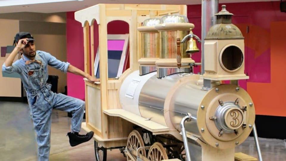 Un homme en habit de conducteur de train, près d'une petite locomotive en bois et en métal.