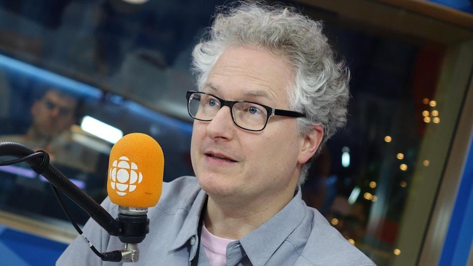 Un homme aux cheveux blancs discute devant un micro au studio 17 de Radio-Canada.