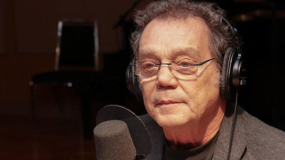 Un homme parle devant un micro dans un studio de radio.