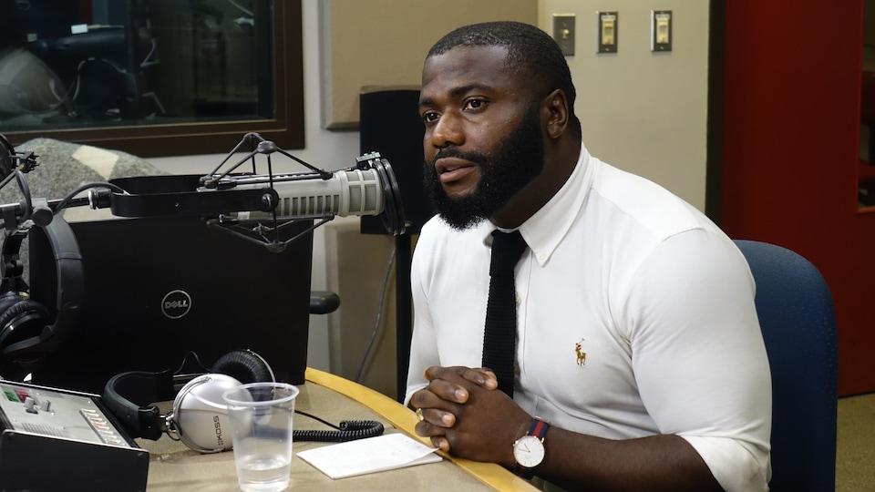 Un homme devant un microphone en studio