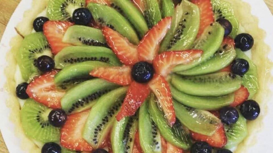 Une tarte aux diffénts fruits déposée sur une assiette.