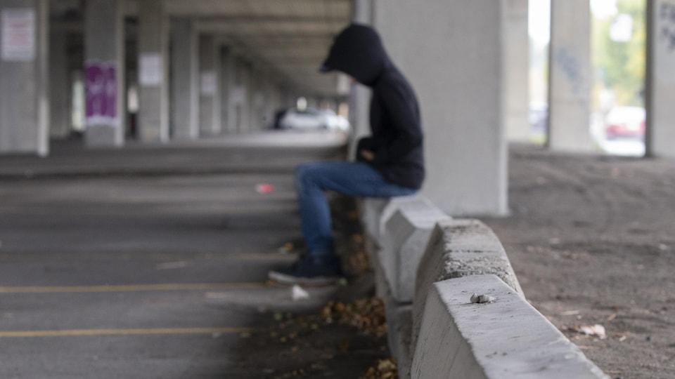Un garçon est assis seul sur un bloc de béton.