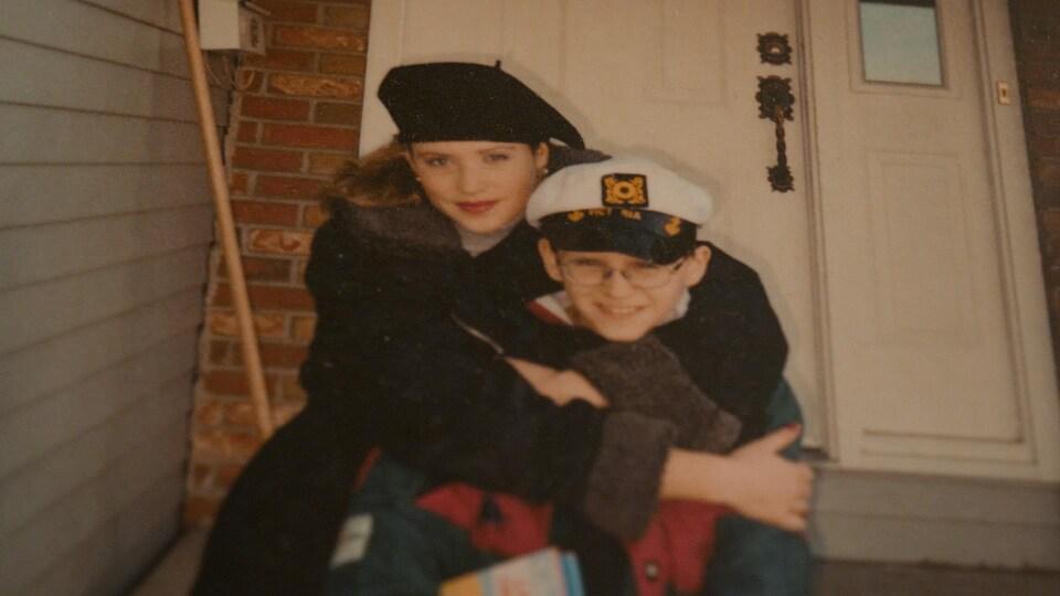 La grande soeur derrière son jeune frère avec ses bras noués autour de son cou