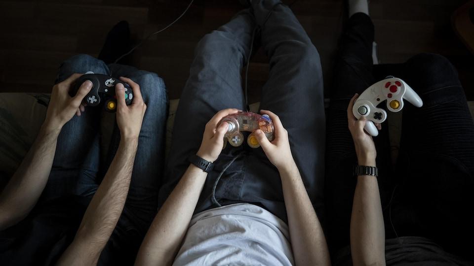 Vue aérienne de trois personnes avec une manette de jeux vidéo en main.