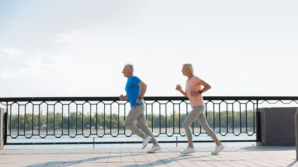 Un couple grisonnant court en vêtements de sports sur une promenade sur le bord de l'eau.