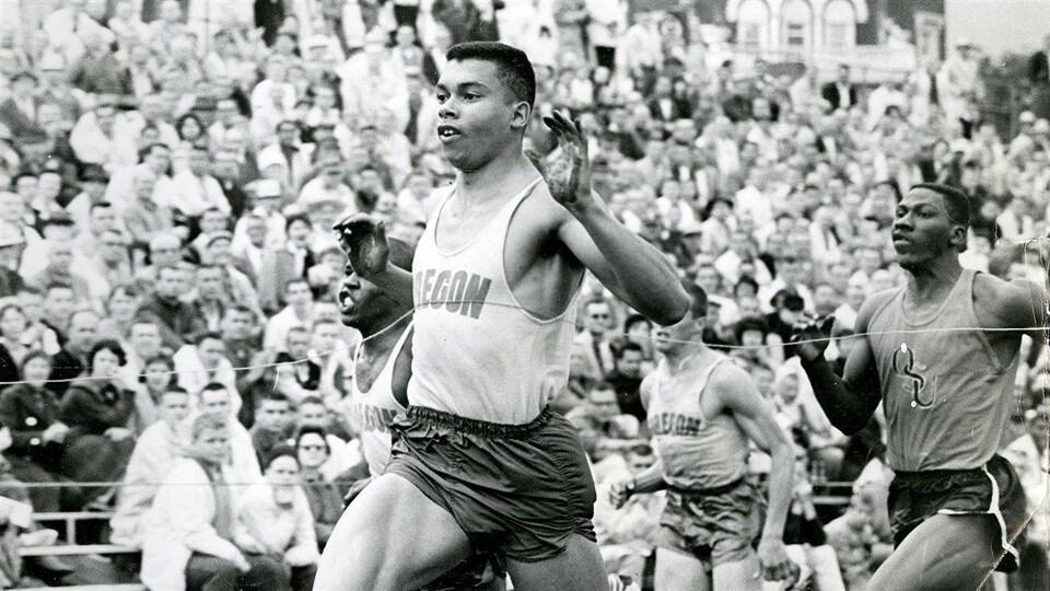 Photo noir et blanc du coureur Harry Jerome franchit une ligne d'arrivée vers 1961.