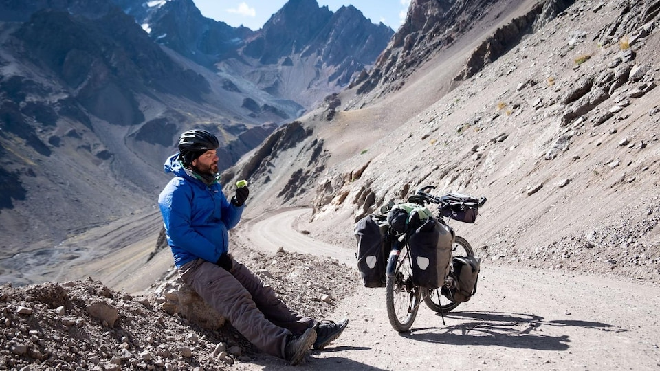 Jonathan B. Roy assis dans un paysage de montagne à côté de son vélo