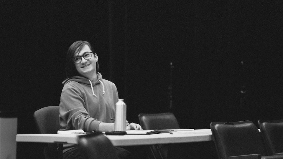 Alex Tétreault assis à une table, souriant.