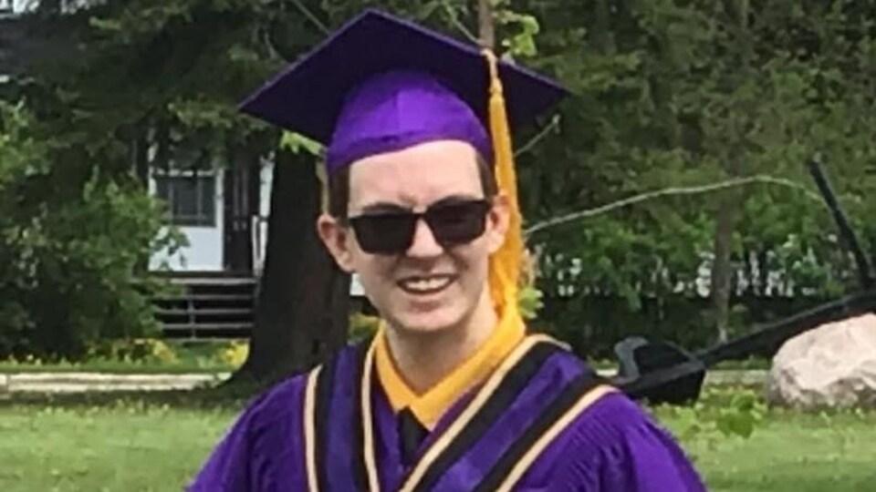 Un jeune finissant en toge de graduation tient un diplome.