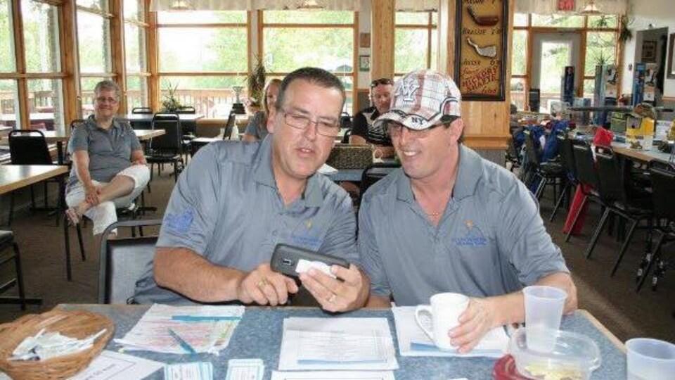 Deux hommes assis à une table regardent un téléphone.