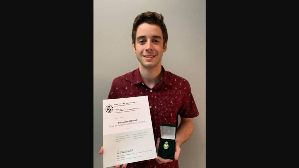 Sébastien tient l'un de ses certificats et sa médaille.