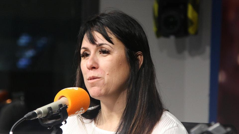 Une femme aux longs cheveux bruns et vêtue de blanc parle au micro.