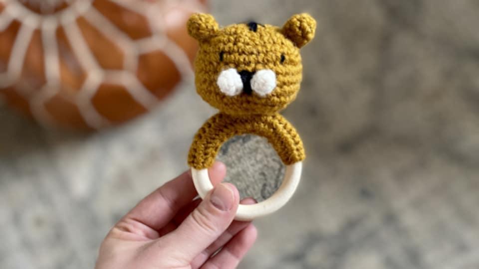 Un petit hochet avec une tête de tigre crocheté, tenu par une main adulte.