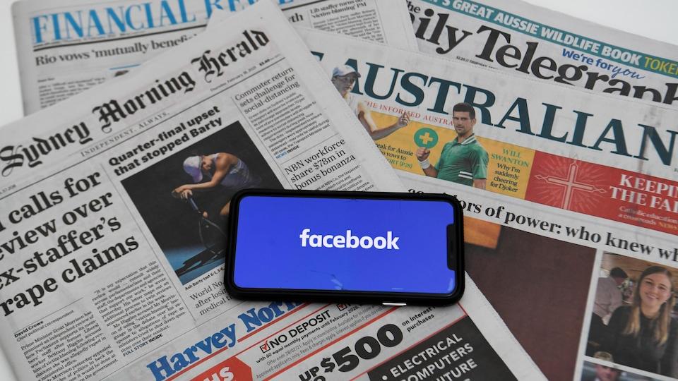 Des journaux avec un téléphone avec le logo Facebook.
