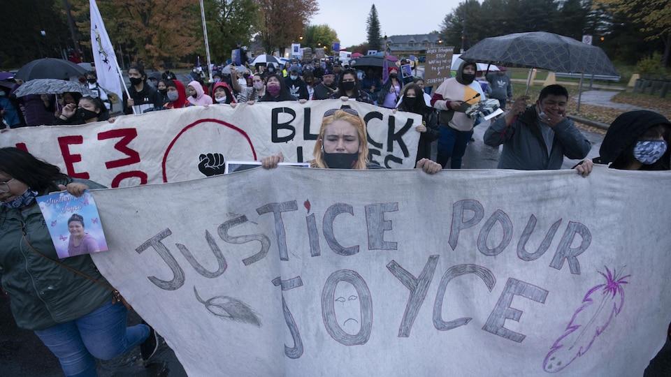 Des personnes tiennent une banderole sur laquelle on peut lire : Justice pour Joyce.