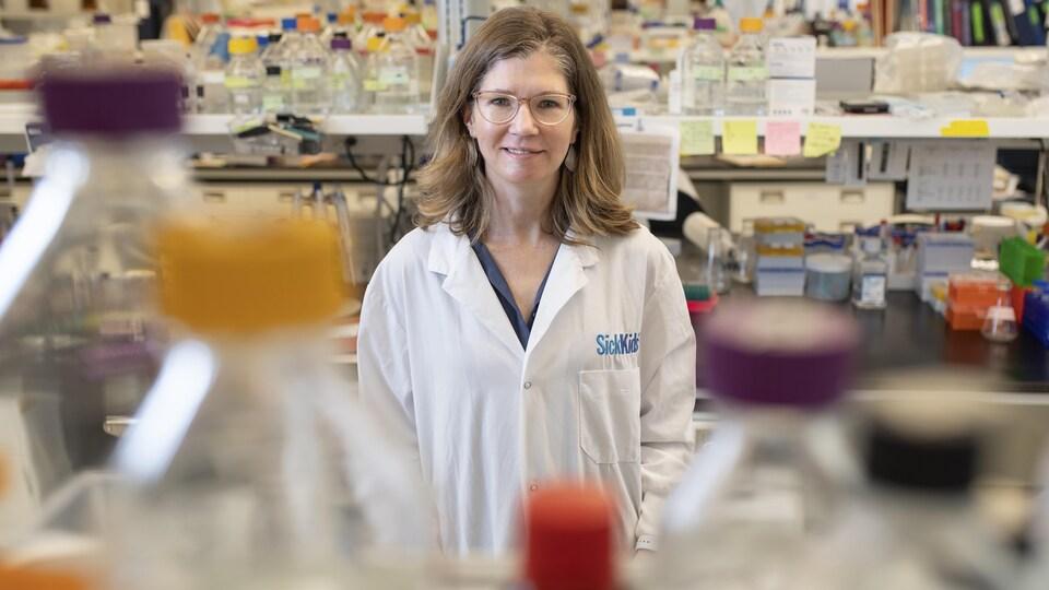 Une femme portant un sarrau se trouve dans un laboratoire.
