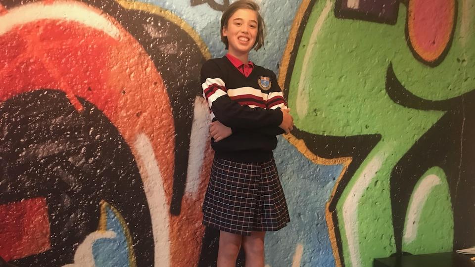 Un garçon portant un uniforme scolaire, dont une jupe à carreaux.