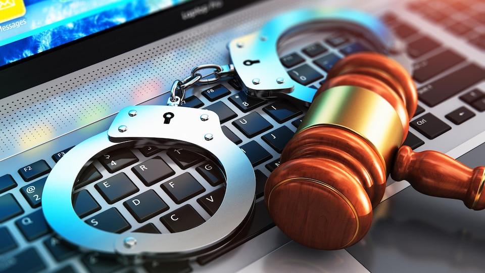 Sur un clavier d'ordinateur repose des menottes ainsi qu'un maillet représentant la justice.