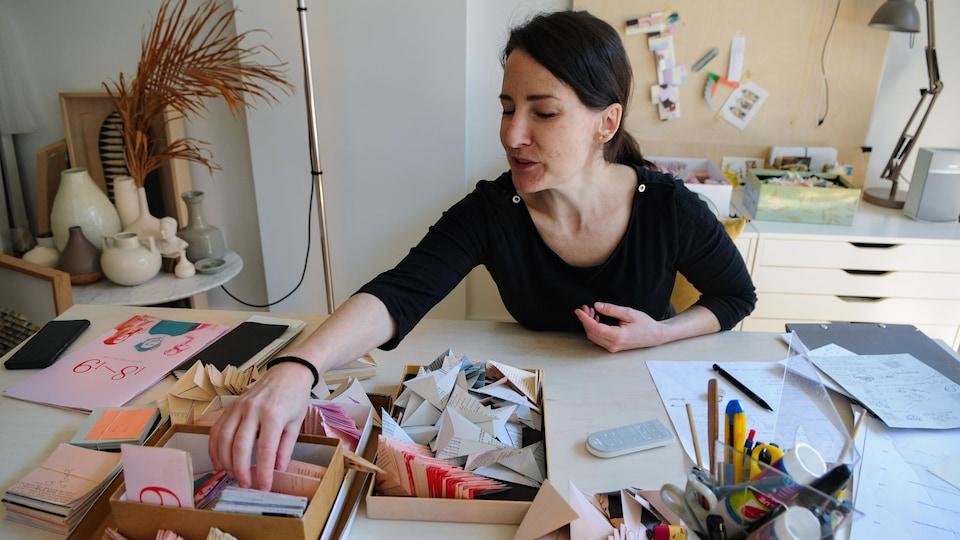 Une femme assise à son bureau pige dans une pile de papiers.