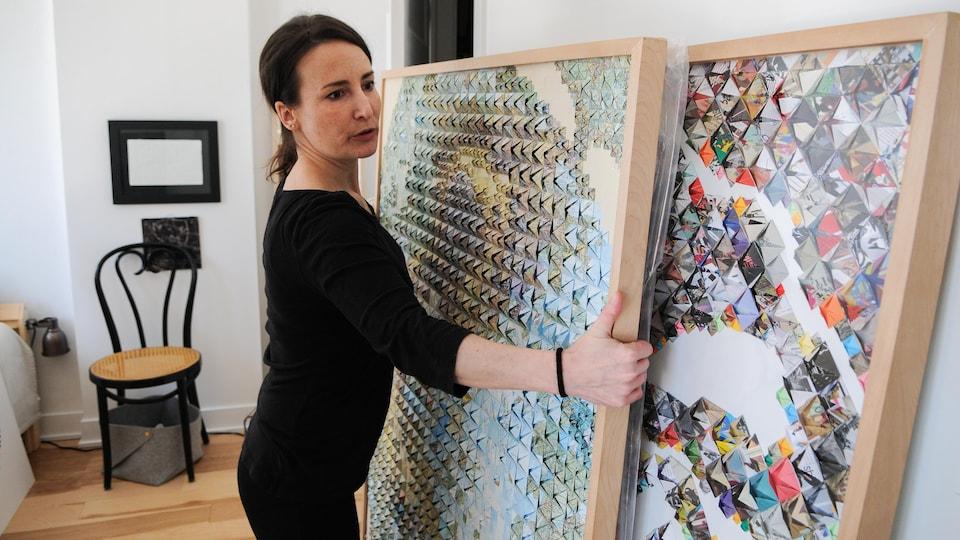 Une femme habillée de noir déplace des œuvres d'art dans un studio.